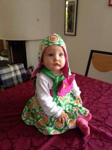 Elina im Trägerkleidchen mit großer Blüte und passender Wendemütze!